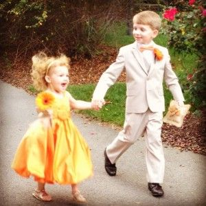 The flower girl and ring bearer walk down the aisle at this outdoor wedding in Raleigh