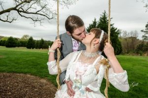 The happy couple share a kiss outside on the swing